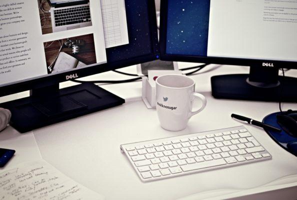 Un bureau avec deux écrans et une tasse de café